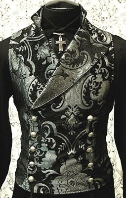 An elegant double breasted vest for formal occasions. A fitted vest made in rich silver and black tapestry fabric with a stand up to collar and wide sweeping lapels. Fastens on the inside with a sturdy button and buttons on the outside with five engraved metal buttons. The vest back and inside lining is made from rich black satin.