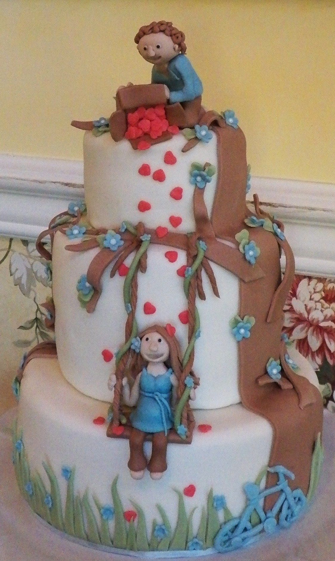 Custom Baby Shower Cake: Pregnant Mommy on a swing. Daddy showering her with love (hearts falling out of a box) Their first date was riding bicycles, they drove on a tandem bicycle at their wedding so the baby shower had to include a bicycle :)