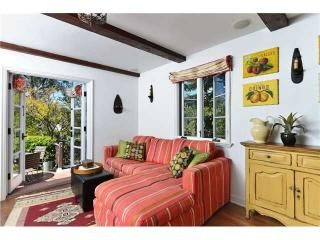Family room off kitchen features a comfortable L sofa in red stripe, with golden rod sideboard. French doors to backyard.