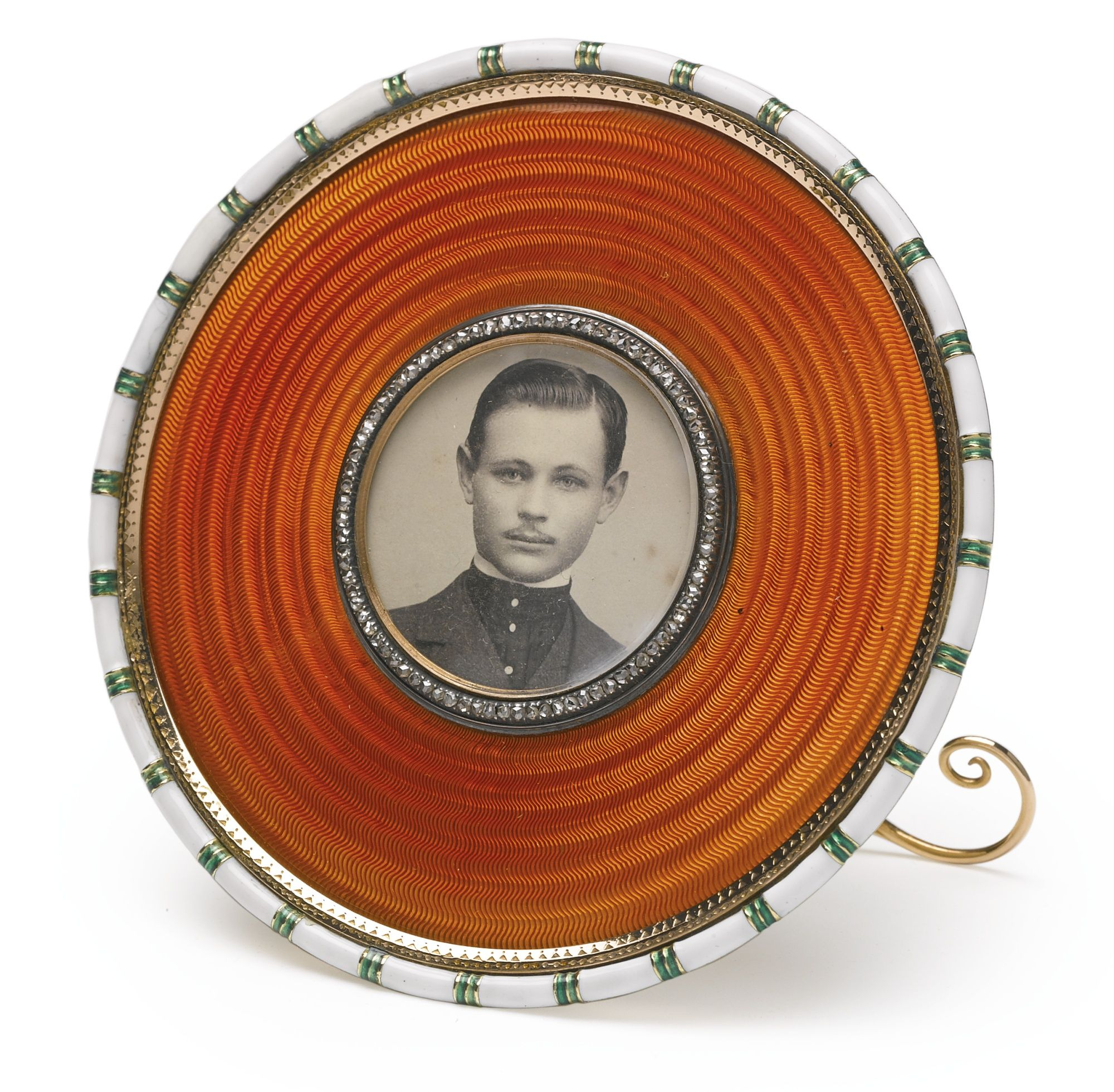 A FABERGÉ GOLD AND ENAMEL PHOTOGRAPH FRAME, WORKMASTER MICHAEL PERCHIN, ST. PETERSBURG, CIRCA 1895 circular, enameled in translucent apricot over concentric guilloché bands, the rim with opaque white enamel relieved by bands of green, the circular aperture with rose-cut diamond bezel, the ivory back with scrolling A-form gold strut, with workmaster's initials, Fabergé in Cyrillic, and 56 standard; also with scratched inventory number 54609, in fitted leather Wartski case diameter 3 in.; 7.6…