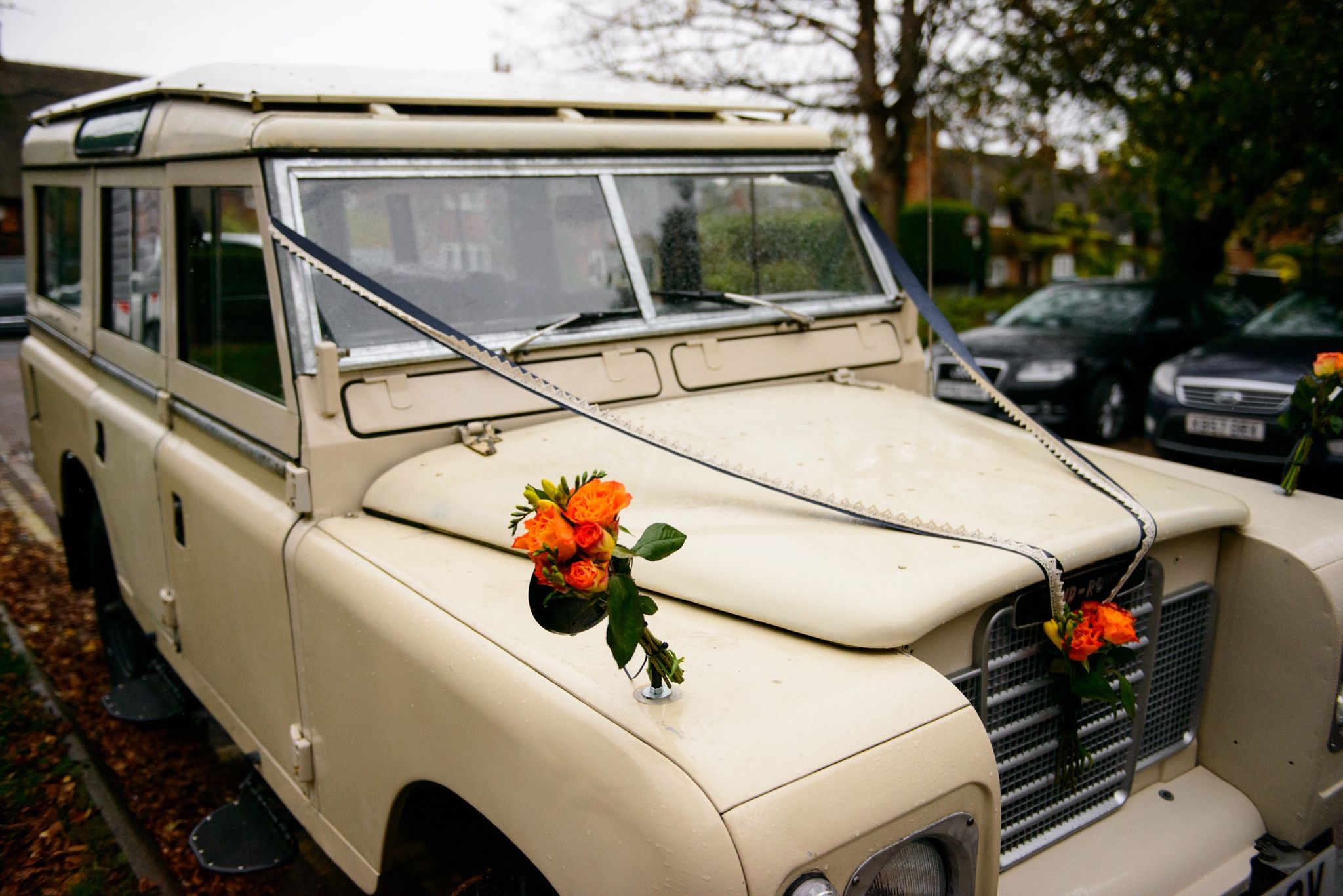 Classic 109 Land Rover wedding decoration Navy satin ribbon overlaid with cotton lace and finished with orange roses and yellow and orange fuchsias.
