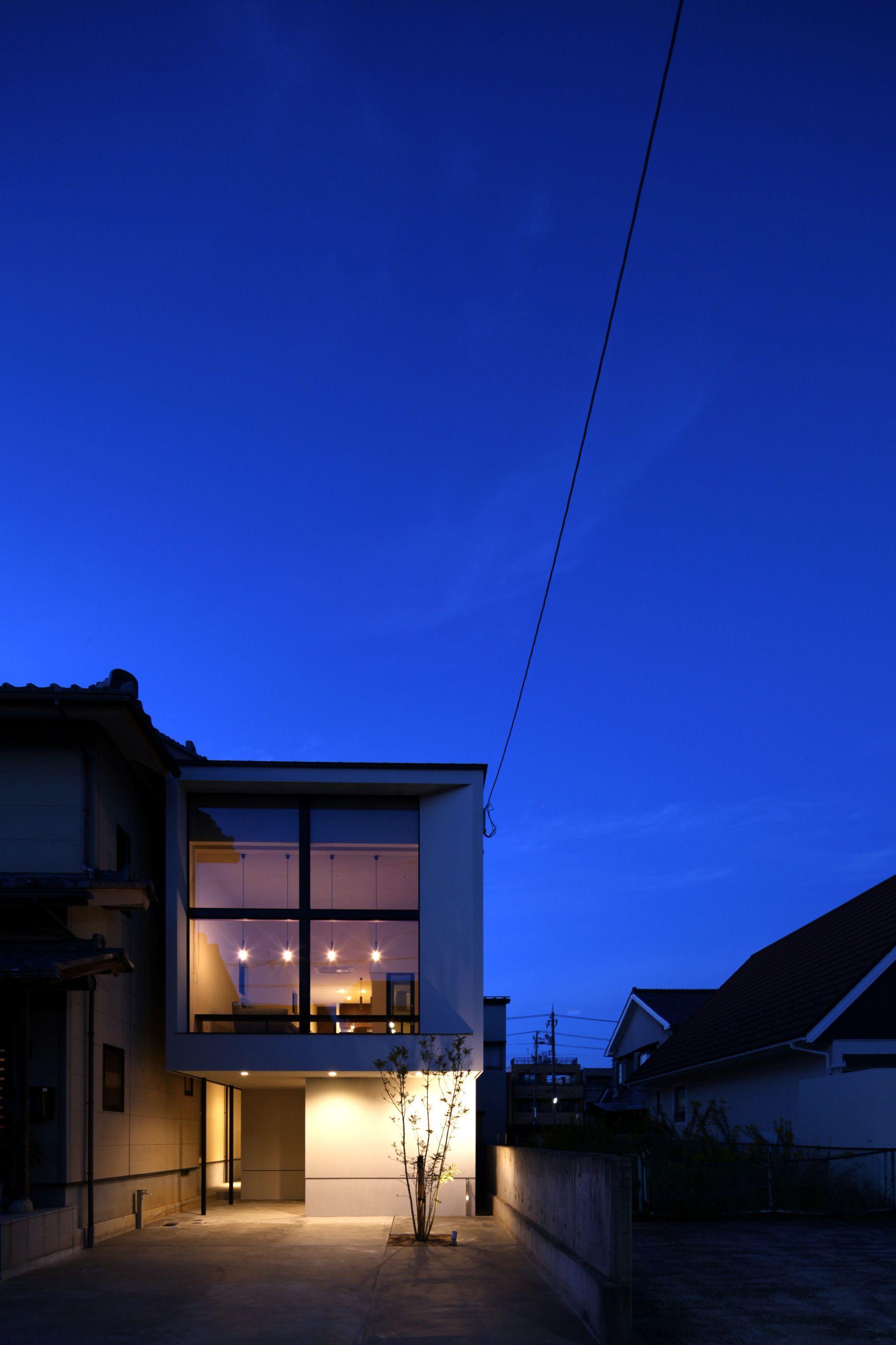 夜は リビングのペンダントライトと外部の照明が建物をより魅力的に見せてくれます 建築 住宅 外観 夜景 駐車場 ミニマル デザイン 照明 House Facade Architects Minimal Design Monotone Lighting ホームウェア 建物 家