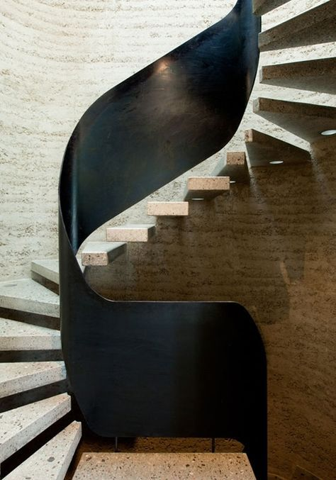 the simplicity of this staircase cantilevered concrete treads off a concrete wall in contrast with the bold statement of using black steel for the swirling guard rail | contemporary & clean staircases that will certainly inspire you | www.pinterest.com/ #inspirationideas #interiordesign #furniture #interiordesigninspiration #staircase