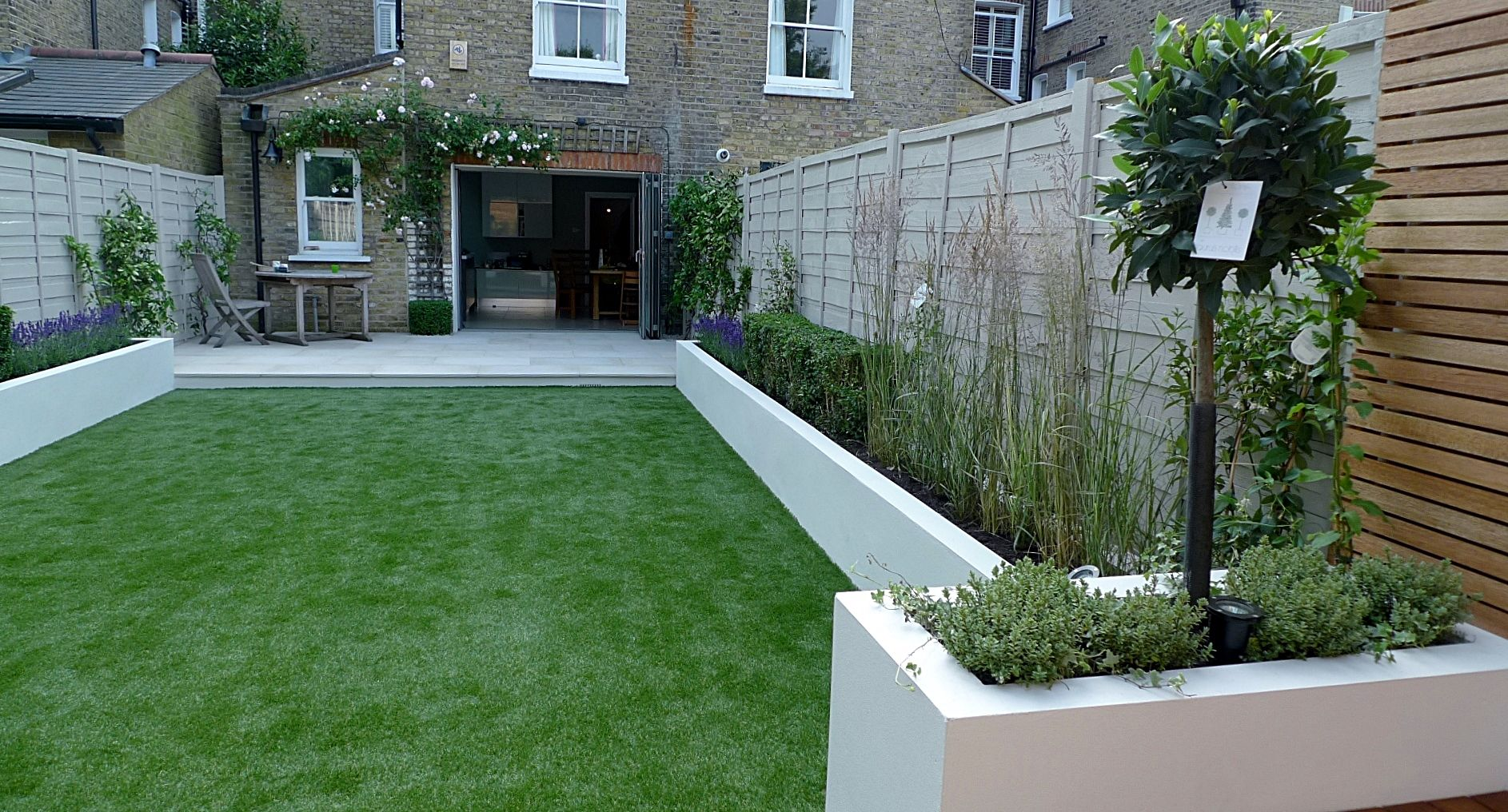 Artificial grass raised beds sawn sandstone paving ...