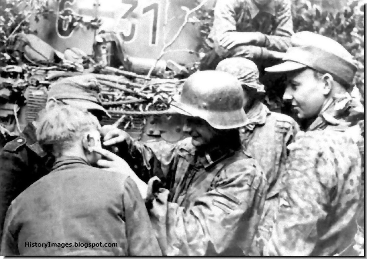 Patching up a wounded comrade. Men from Hitler Youth (Hitler Jugend) Division