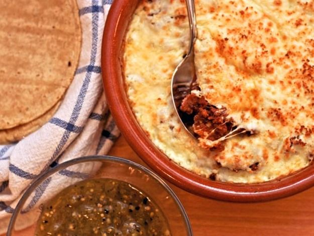 It didn't take long to convince my wife that we would indeed be eating a bowl of bubbling cheese for dinner. It would be stuffed with crumbled Mexican chorizo, I explained, then spooned into tortillas doused with a vibrant tomatillo salsa. It would be ready in about 15 minutes—as simple as grating some cheese, cooking the chorizo, and mixing them together to bake. Just think of it as a Mexican-style fondue (\