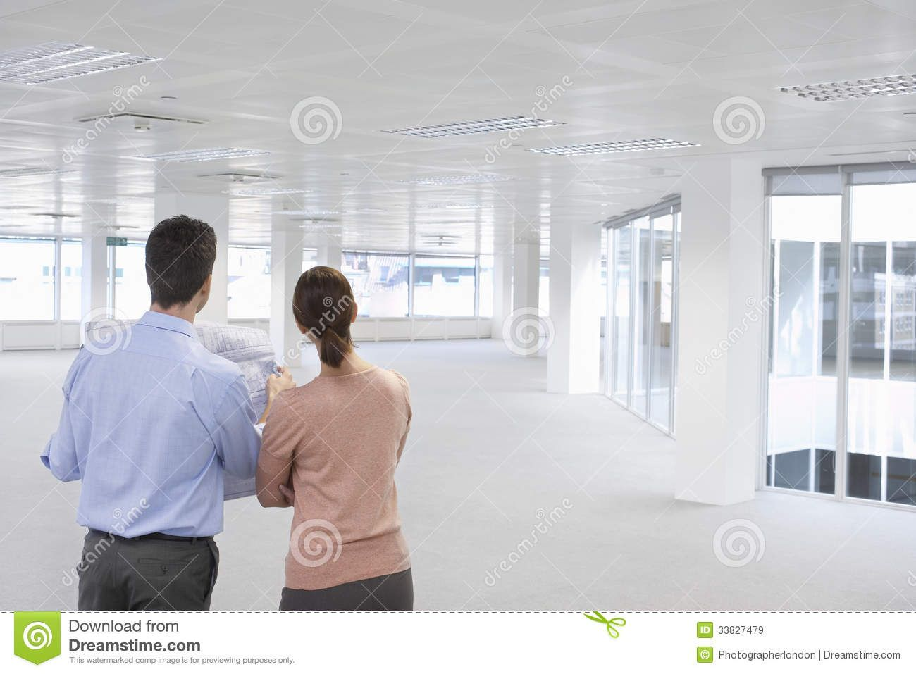 Business People Looking At Plan And Empty Office Space