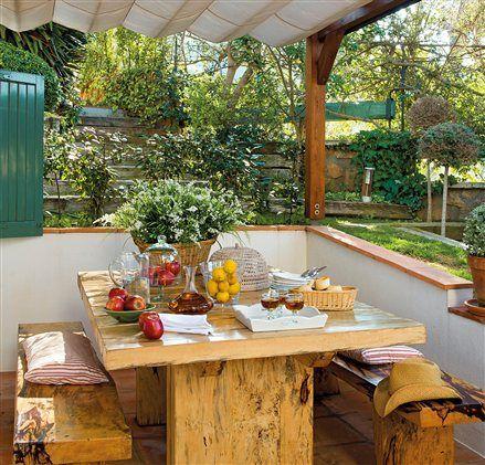 Comedor exterior con mesa y bancos de madera bajo pérgola ...