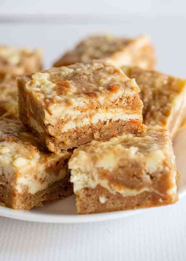 Carrot Cake Bars - These carrot cake bars are so moist and delicious! They have a sprinkle of cinnamon and a cheesecake swirl in them. They're the perfect Easter dessert bars.