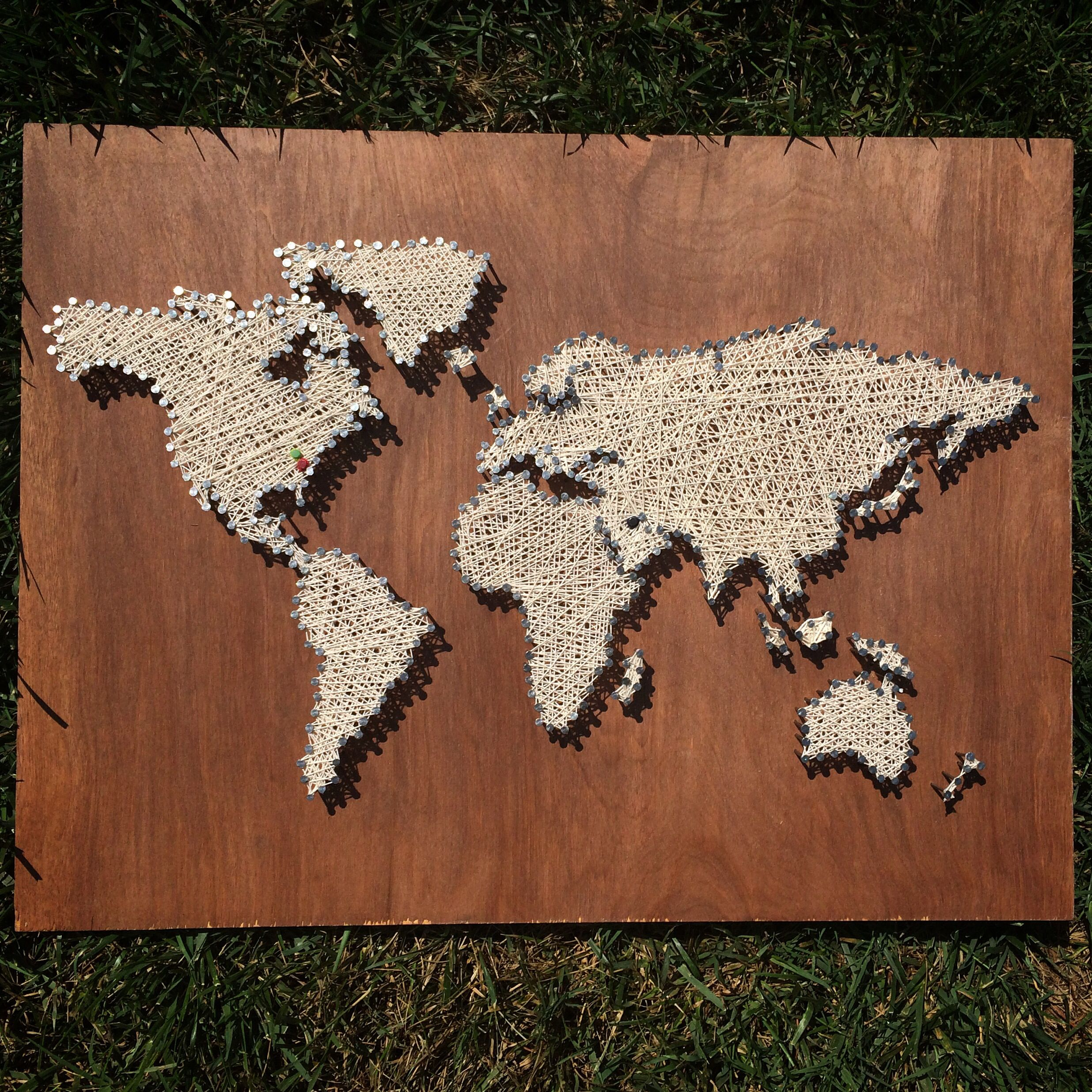 World map string art - look closely and you'll see colored dots over Kuwait, Charleston, and Charlotte. This was custom ordered to represent a family's cross cultural heritage.