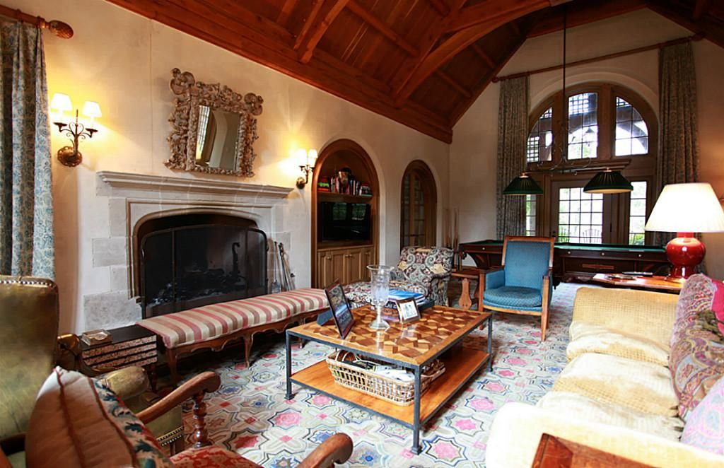 Another view of Family Room/Den which highlights the grand fireplace with limestone surround and shows the  divided light door and arched windows leading to rear yard
