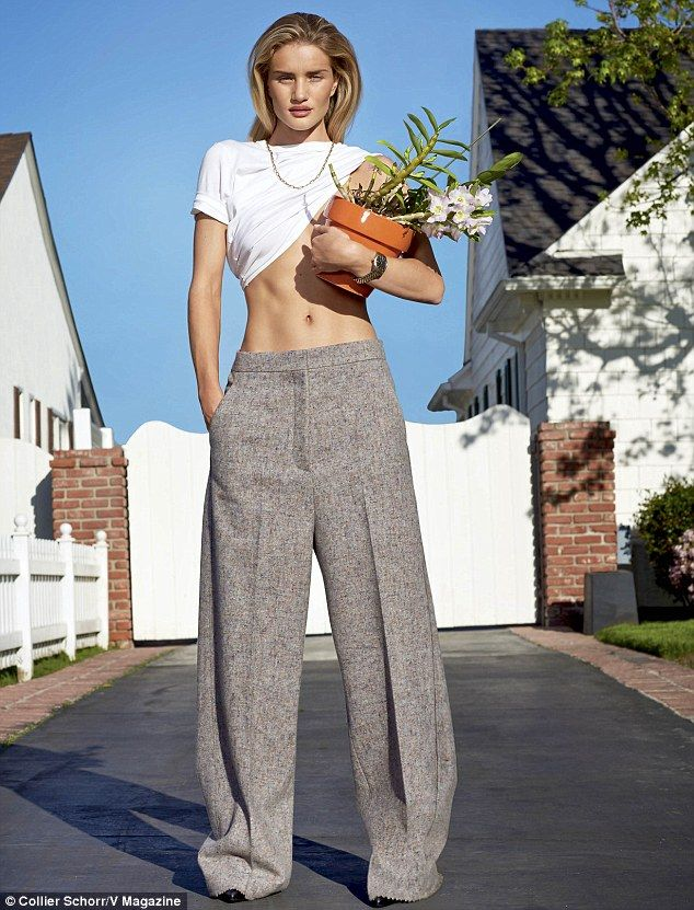 Tanned and toned: Rosie showed off her taut tummy as she modeled a pair of tailored grey t...