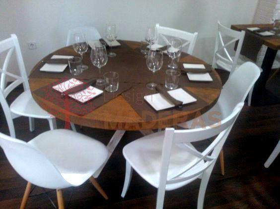 Mesa redonda de comedor, de madera maciza con tablero de tono roble oscuro y patas de madera blancas decapadas.