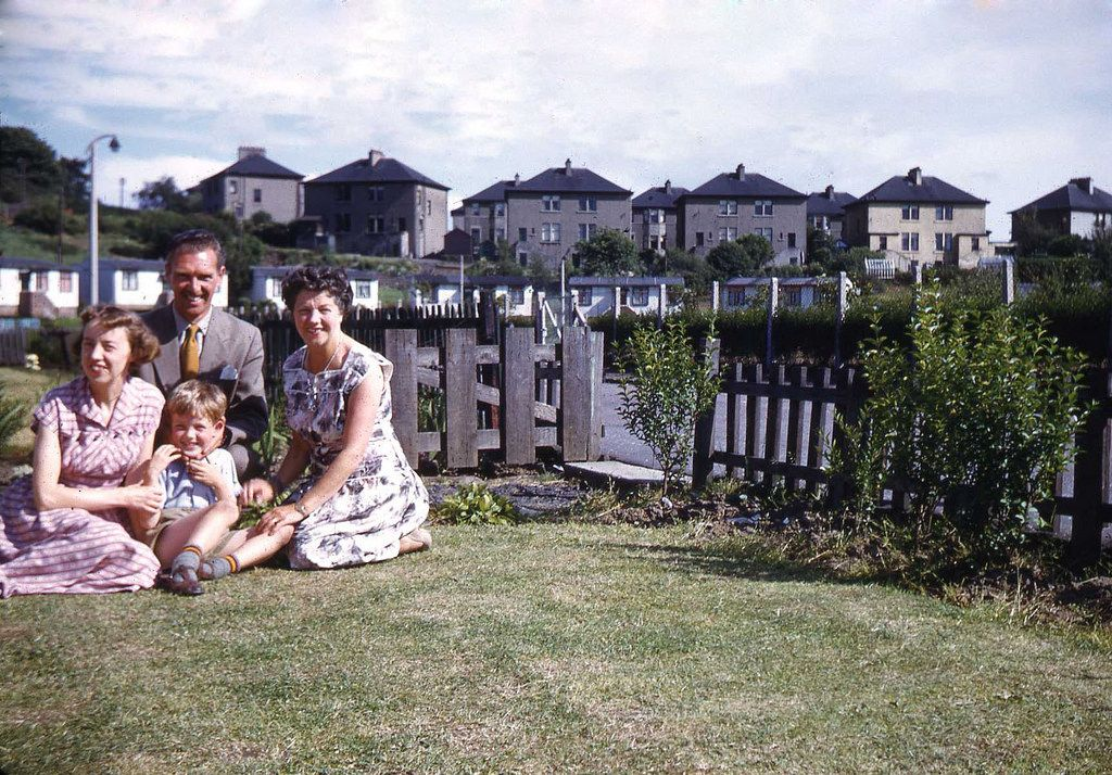 On the front lawn of the prefab at Gallowhill, Paisley with my mother, Unmcle Eric and Aunt Jean, July 1957. The houses on the hill in the background are on Arkleston Crescent. Professionally scanned by Derek Lunn, Photographer, from one of my father's colour slides.