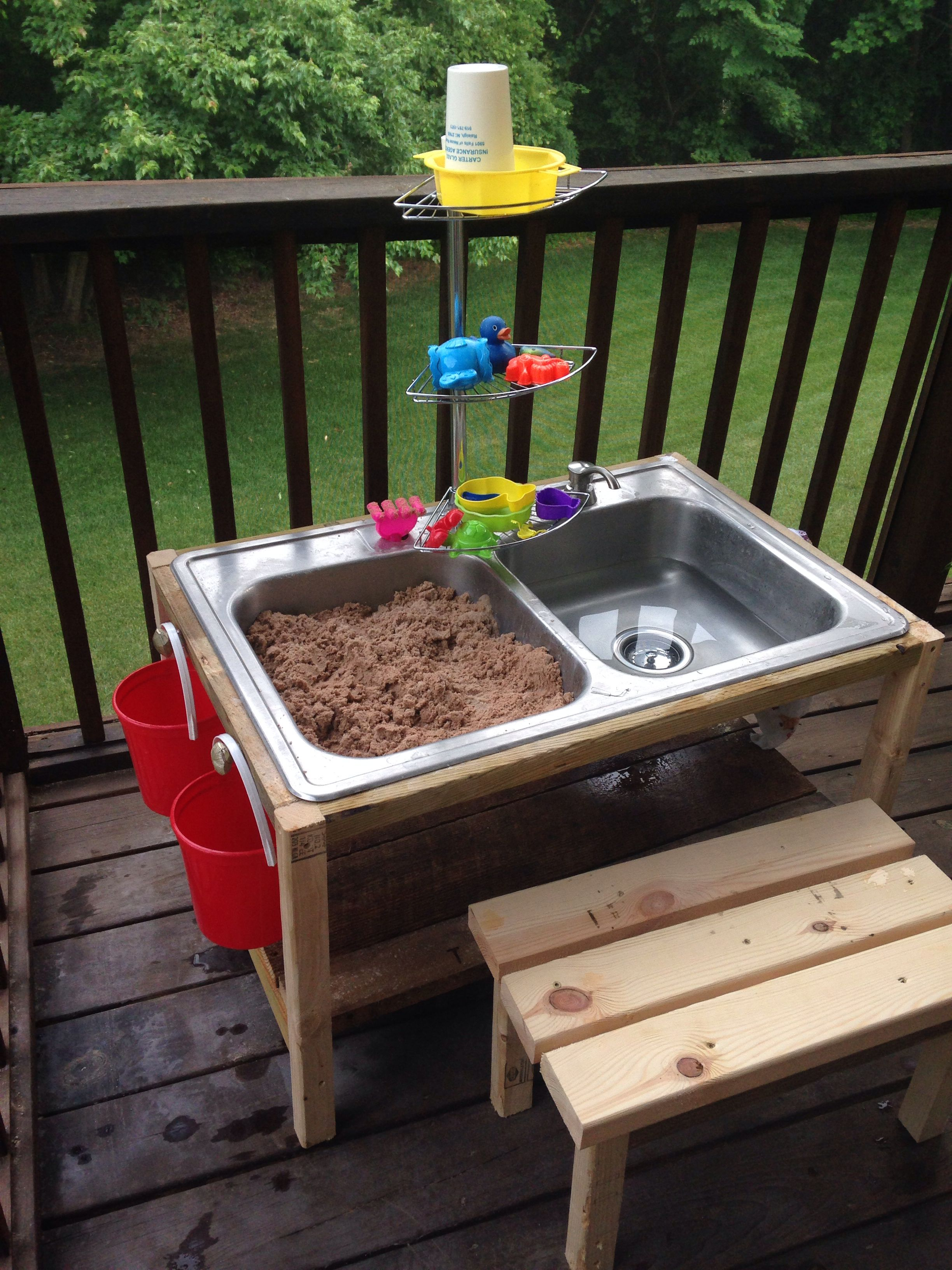 DIY sand and water table made from a thrift store kitchen sink, palette wood and leftover wood from other projects. Add knobs to the side and build a bench to go with it! Super cheap and fun project!