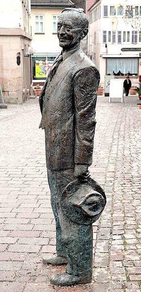 """Escultura de Hermann Hesse: """"Entre quedarse y seguir"""". Diseñada por el escultor Kurt Tassotti, esta estatua de bronce de tamaño real fue presentada en Calw en el 125 Cumpleaños del escritor. La figura lo muestra a los 55 años de edad, durante su última visita a principios de 1930 en Calw."""