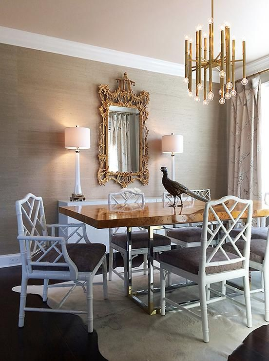 A Jonathan Adler Meurice Chandelier Illuminating Stainless Steel And Burl Wood Dining Table Bond Lined With White Bamboo Chairs