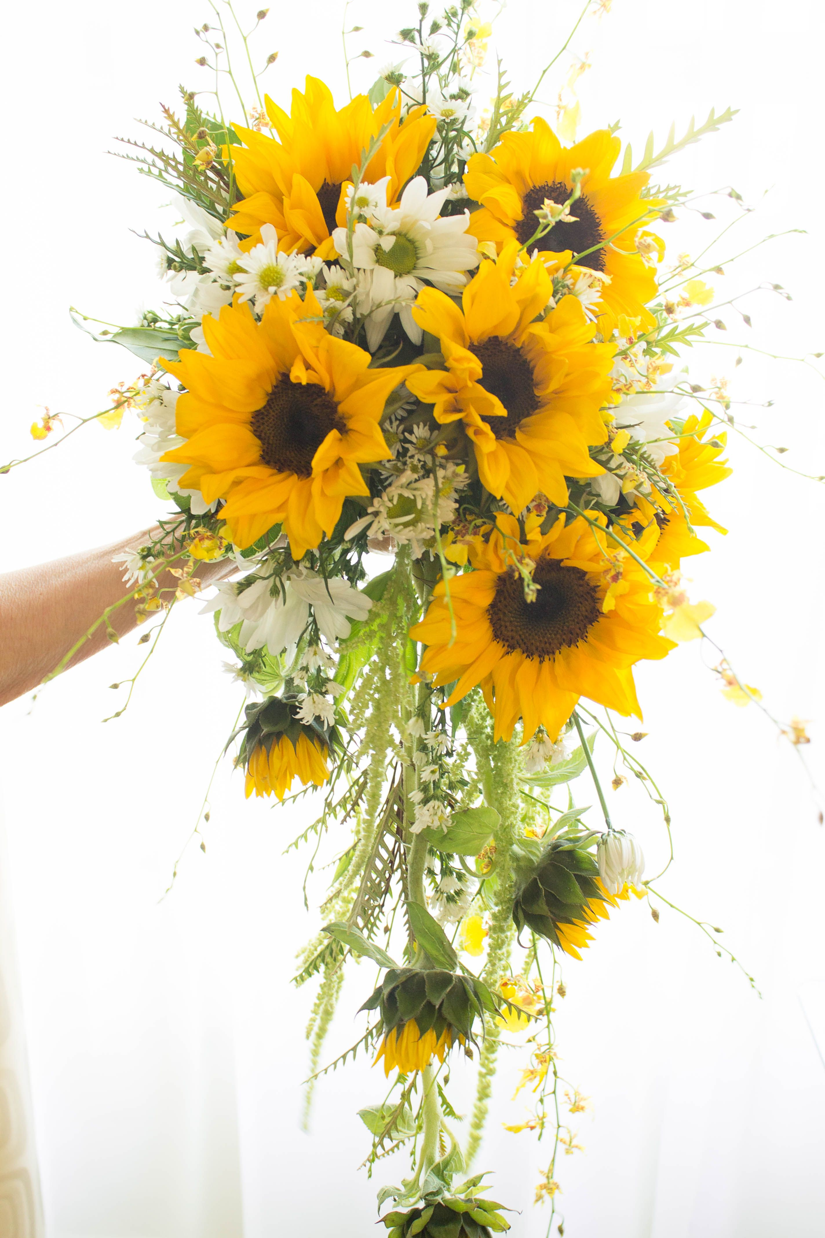 Cascading Bouquet designed with Oncidium orchids, sunflowers and greenery.  Designed by CS Events and Floral.  Las Vegas, NV.
