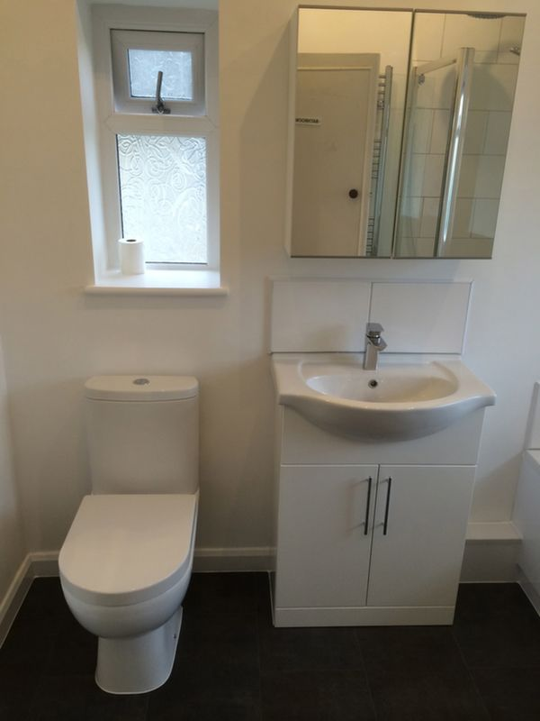 Floor Mounted Vanity Mirror W/ Backsplash In A Bathroom Installation By UK  Bathroom Guru