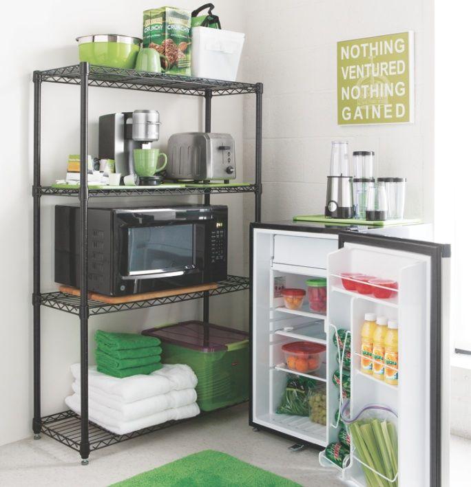 Small Kitchen Area Fridge Next To Shelves That Holds