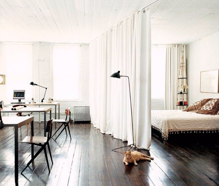 Curtains create a small bedroom area on this studio apartment | www.masterbedroomideas.eu #tinybedroom #studiobedroom #smallbedroomdecor #smallbedroom #bedroomideas