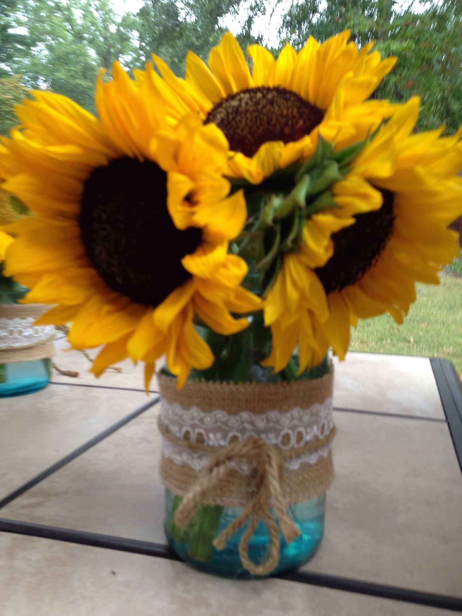 A vintage blue jar burlap ribbon hot glue gun fresh sunflowers