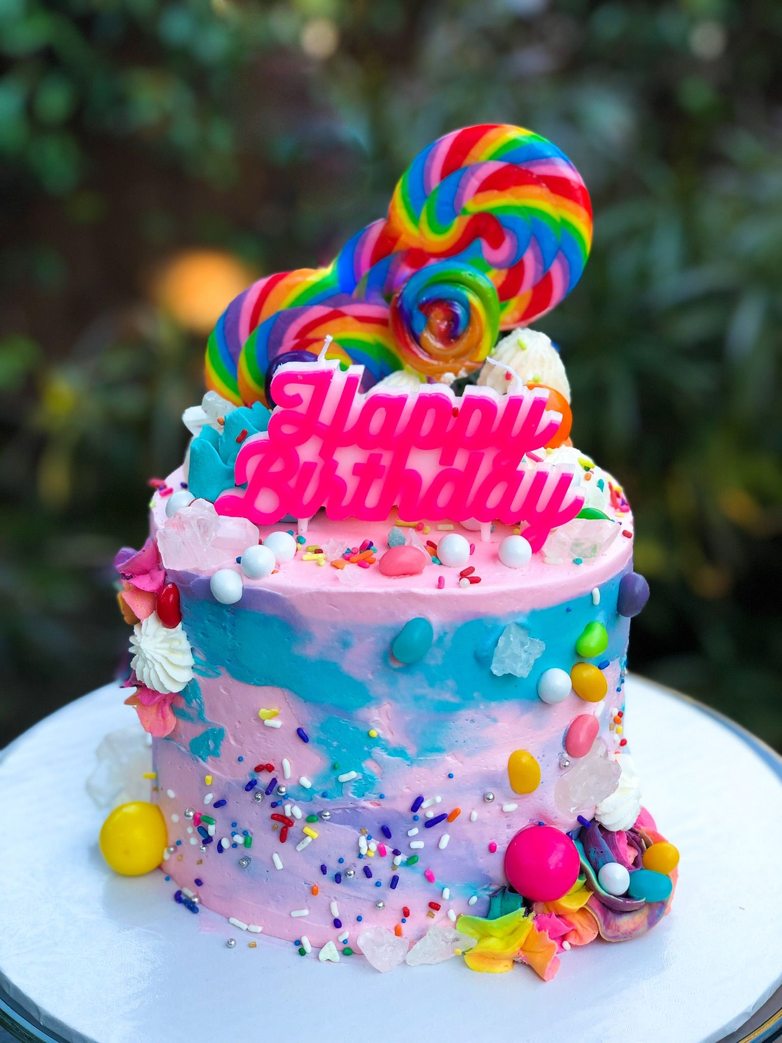 Rainbow overloaded birthday cake with candy and lollipops