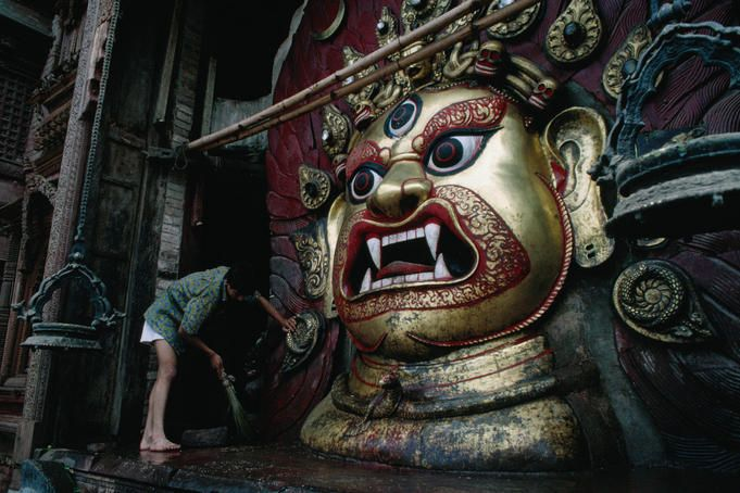 Kathmandu, Nepal.  Sweeping around the horrible face of Seto (white) Bhairab in Durbar Square, Kathmandu, the huge mask dates from 1794. Most of the year it is hidden behind lattice gates.    Read more: http://www.lonelyplanet.com/nepal/kathmandu/travel-tips-and-articles/2281#photo-857-10#ixzz1zbBwXS28