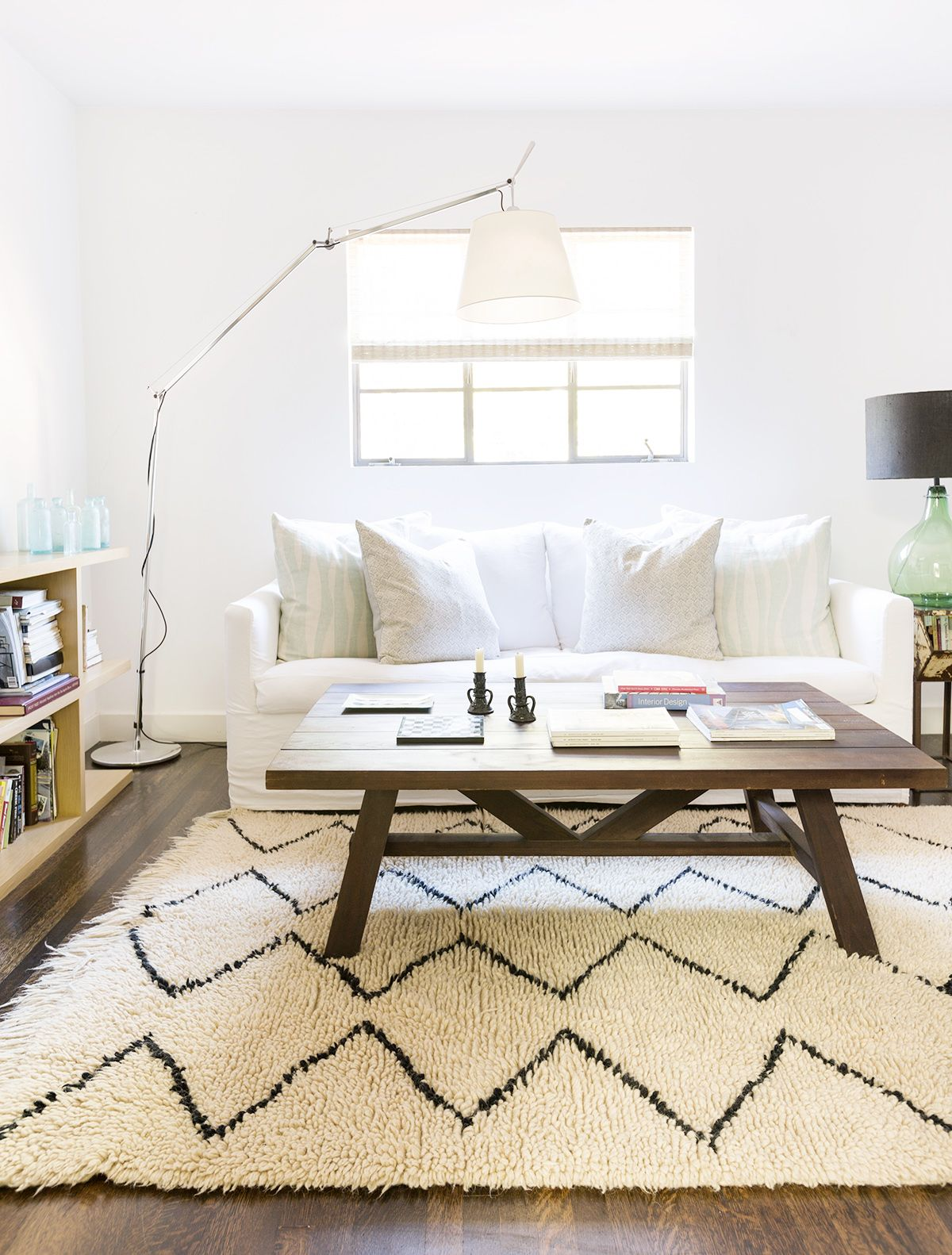 White living room with white sofa, wood coffee table, and modern floor lamp