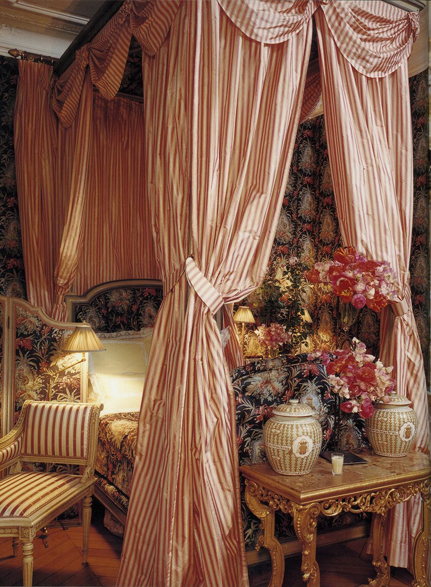 Carolyne Roehm's Paris bedroom is upholstered with intricate Napoleon III toile, making for a dramatic backdrop. The Louis XVI bed, swathed in striped taffeta, exudes opulent secrecy. - Photographed by François Halard, Vogue, June 1996