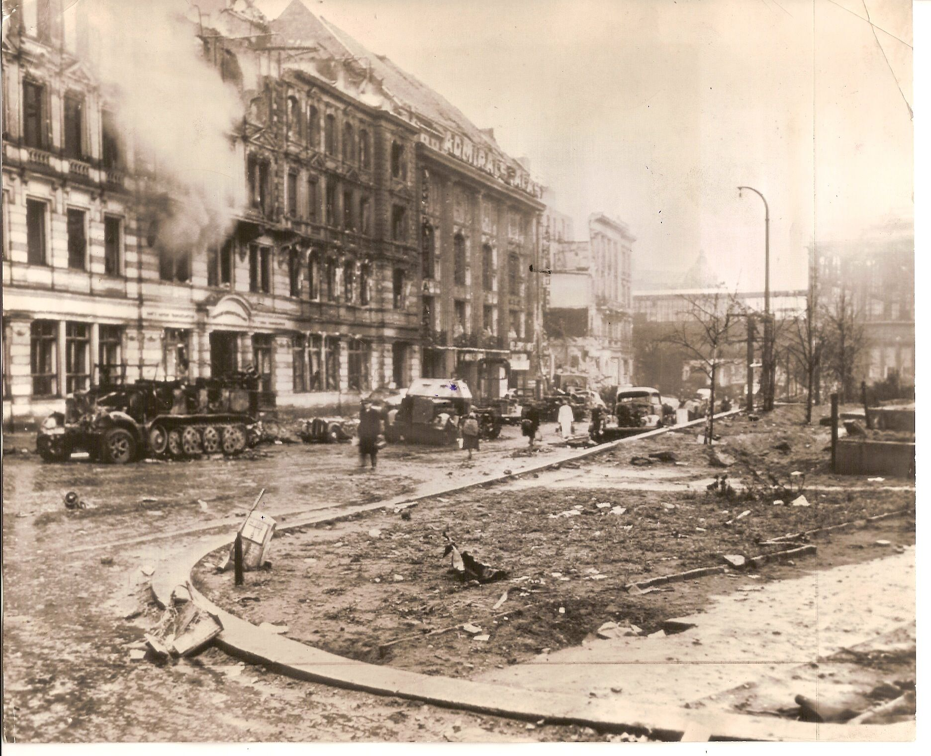 """An attempt to breakout on May 2nd 1945, Berlin   The building with a huge signboard was the Admiralspalast in the The Friedrichstraße 101, a major culture and shopping street in central Berlin. Background the """"S-Bahnhof Friedrichstraße"""" slides across the street. This series of the well known photo of a blown-up armored car in Berlin was actually one of the Schwedish Kompanie's vehicles in the 11th SS Nordland Division. It could have been company commander Pehrssons command vehicle that was…"""