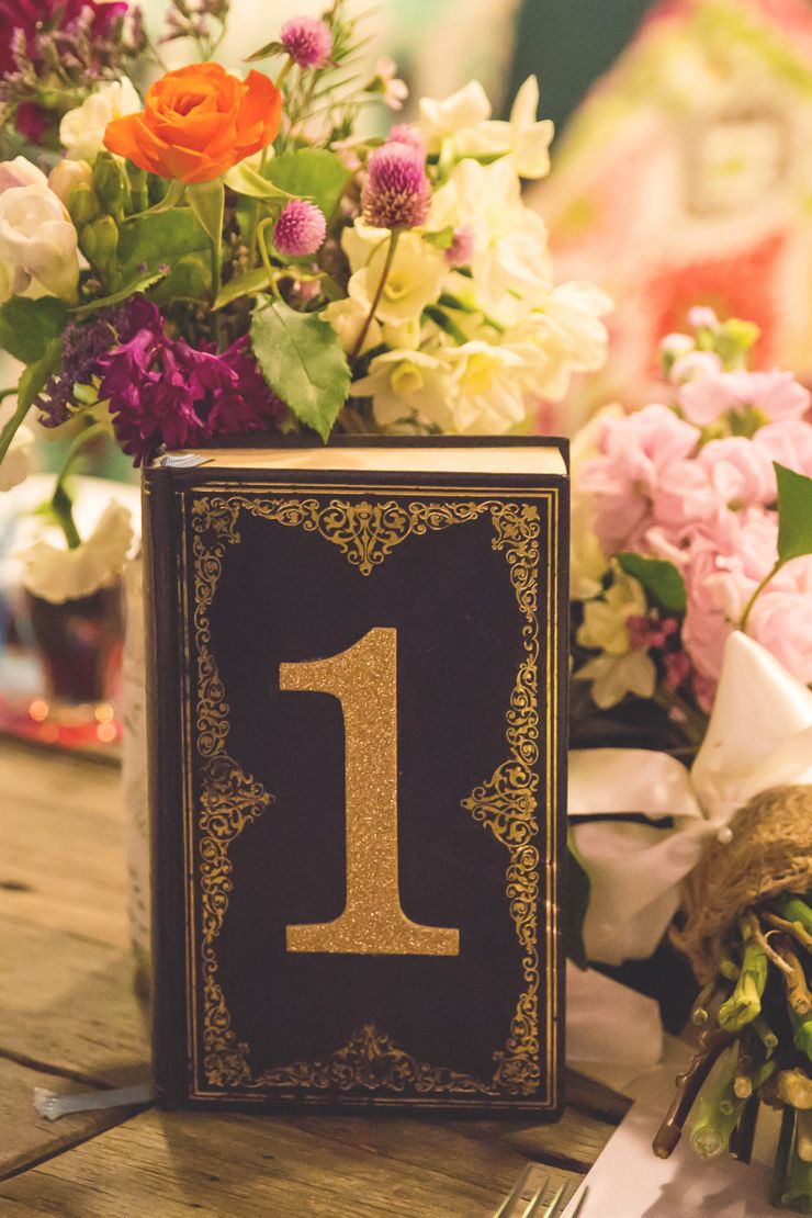 Vintage story books were used as table numbers - the guests read them aloud at the reception!   Jenna Fahey-White   See more: http://theweddingplaybook.com/colourful-vintage-diy-wedding/