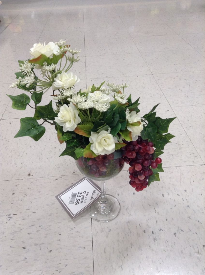 Floral arrangement of white roses, mini ivy, grapes in a wine glass ...
