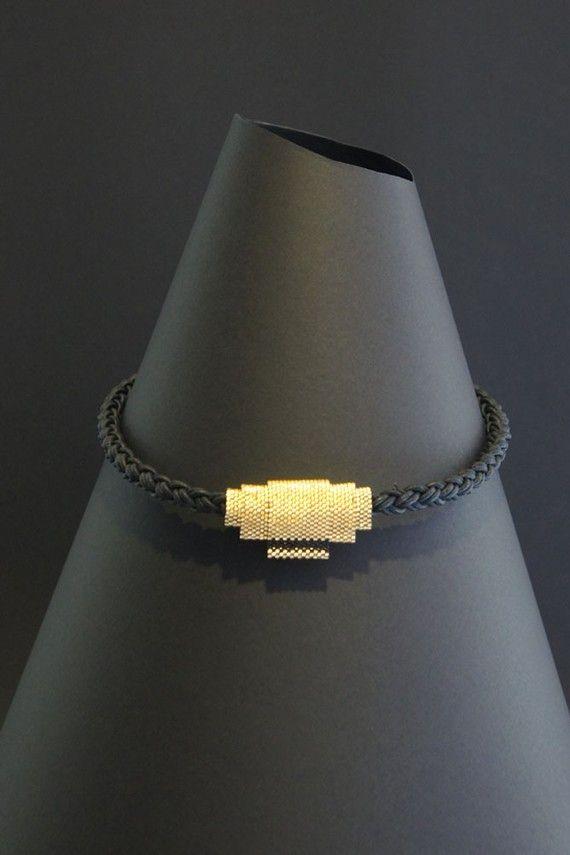 A Strip of Black (Peyote stitch of Gold Miyuki Beads on a thick leather cord. )