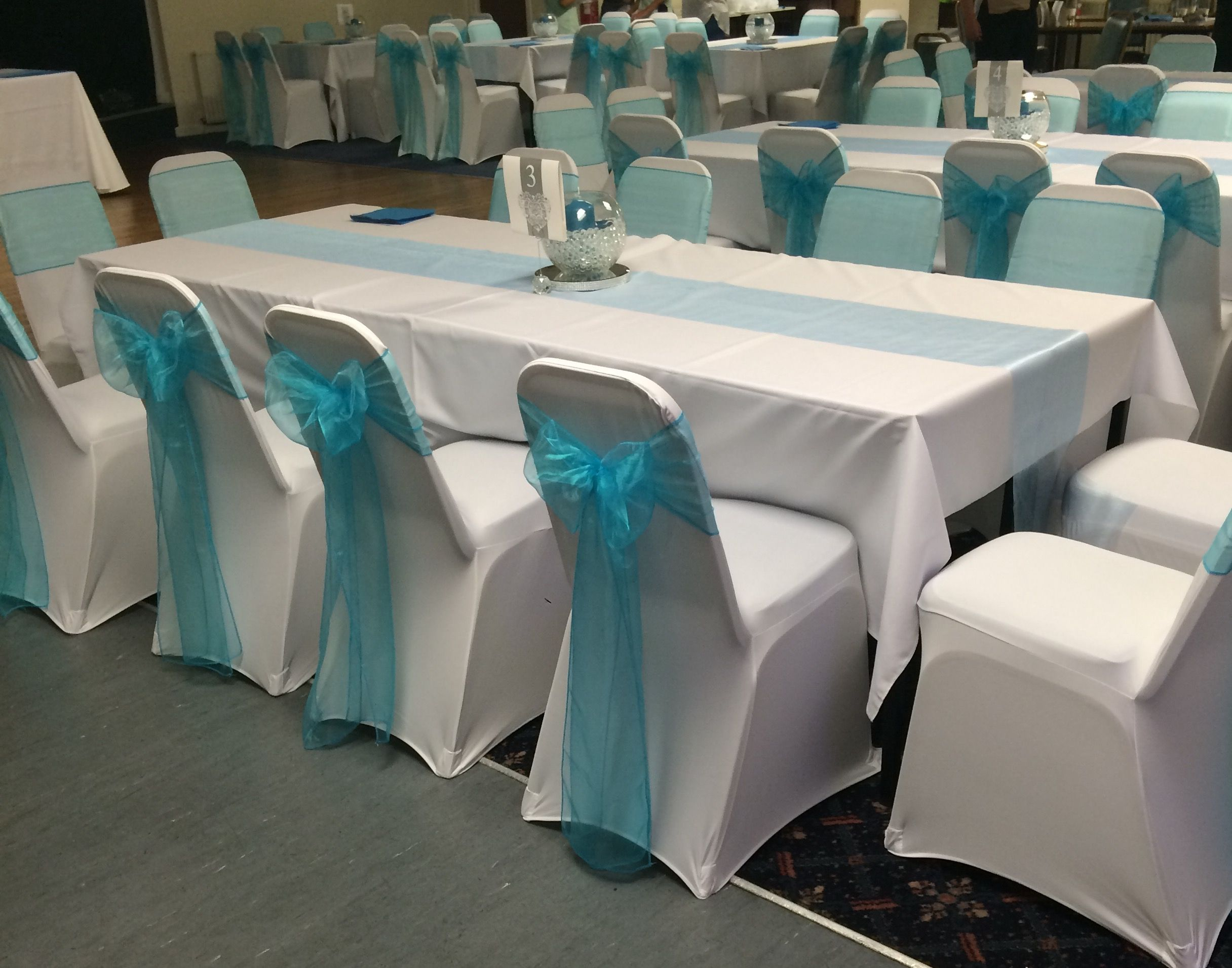 Pastel rainbow sashes on white chair covers in maesteg South