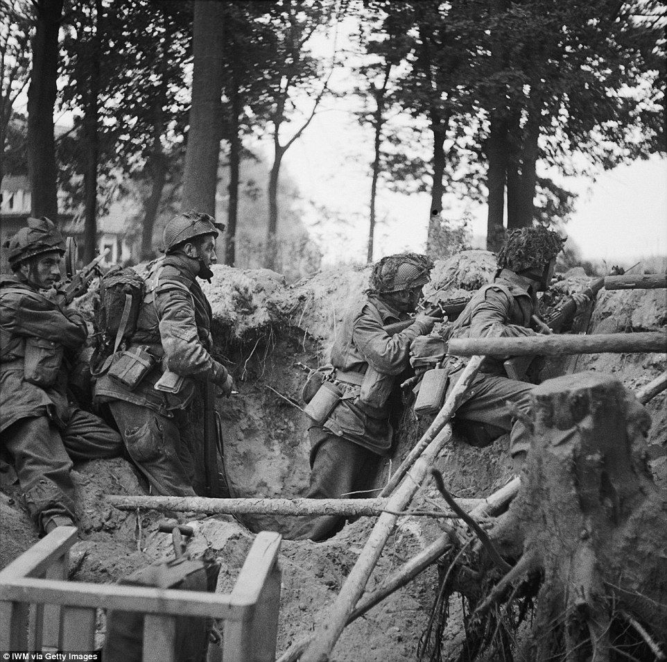 Men of the 1st Battalion Parachute Regiment take cover in a shell hole in 17 September 194...