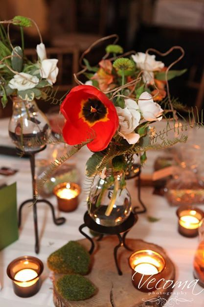 Centerpieces with light bulb vases holding the flowers on a wood slab with moss. Gorgeous! #woodencenterpieces #mosscenterpieces Vecoma at the Yellow River