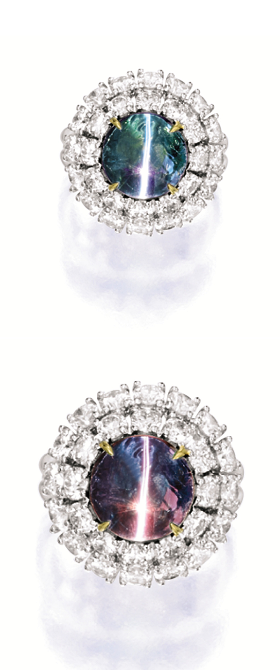 CAT'S-EYE ALEXANDRITE AND DIAMOND RING. Centring on a round cabochon cat's-eye alexandrite weighing 4.08 carats, surrounded by a double-frame set with brilliant-cut diamonds together weighing approximately 3.05 carats, mounted in 18 karat white and yellow gold