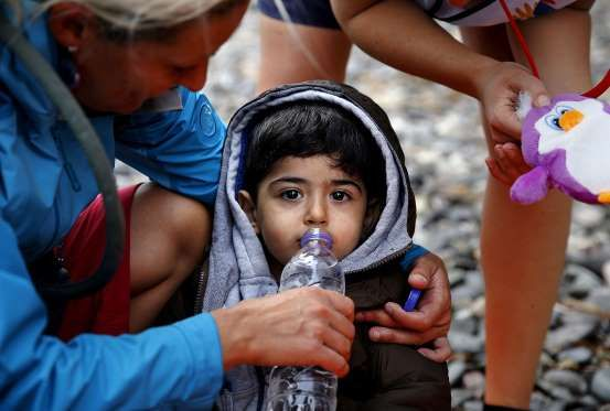 Volunteers give water and toys to an exhausted Syrian refugee child soon after he and his family arr... - Yannis Behrakis TPX IMAGES OF THE DAY/Reuters