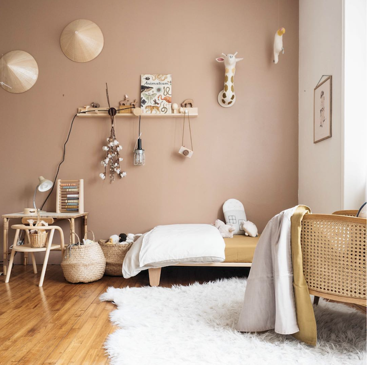 A charming children's room with peach-brown walls and natural wood ...