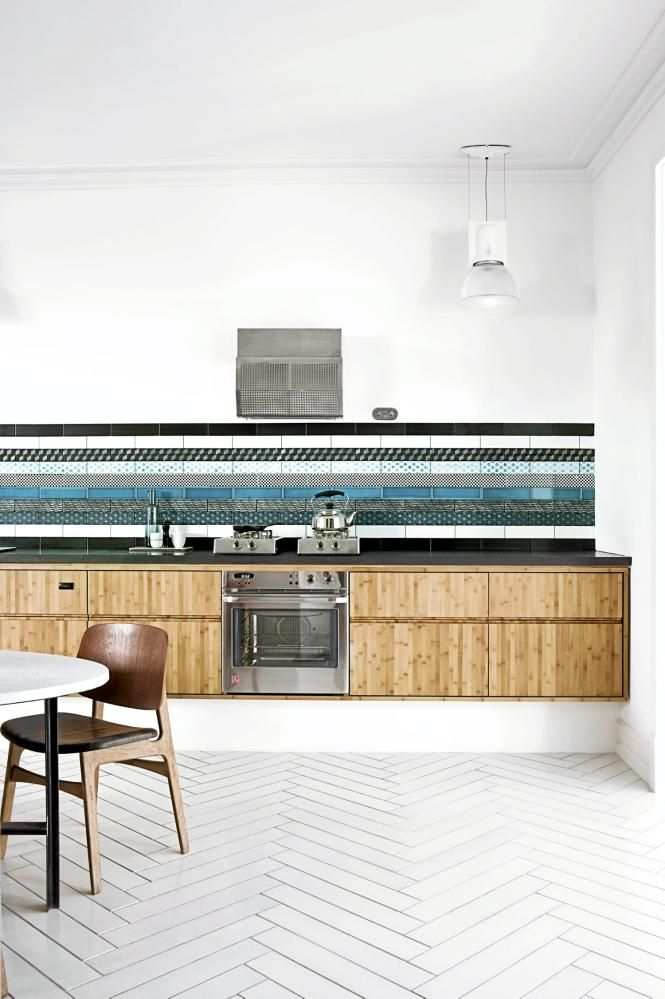 Modern kitchen. Beautiful tiled splashback with a timber cabinets. The herringbone flooring tops of the space