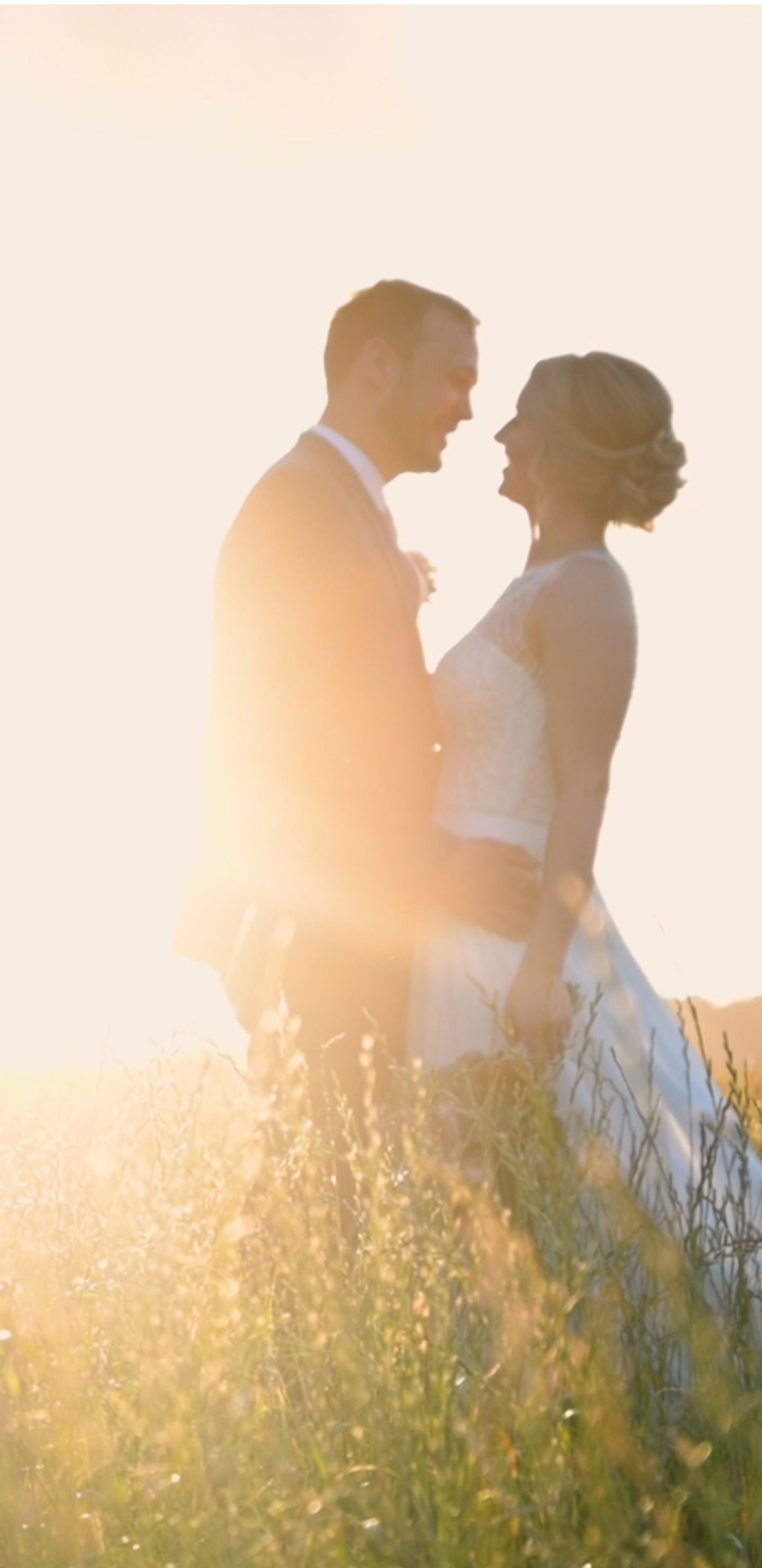 Bride and groom looking at each other in field during sunset