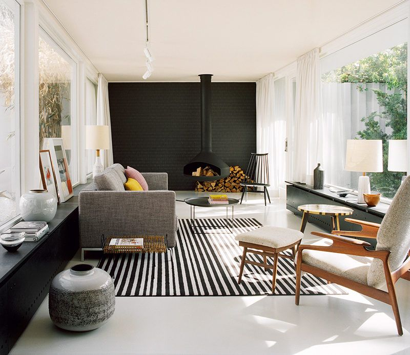 A Hanging Fireplace And Black Accent Wall Stand Out In This Modern Living Room Atrium House House Interior Mid Century House