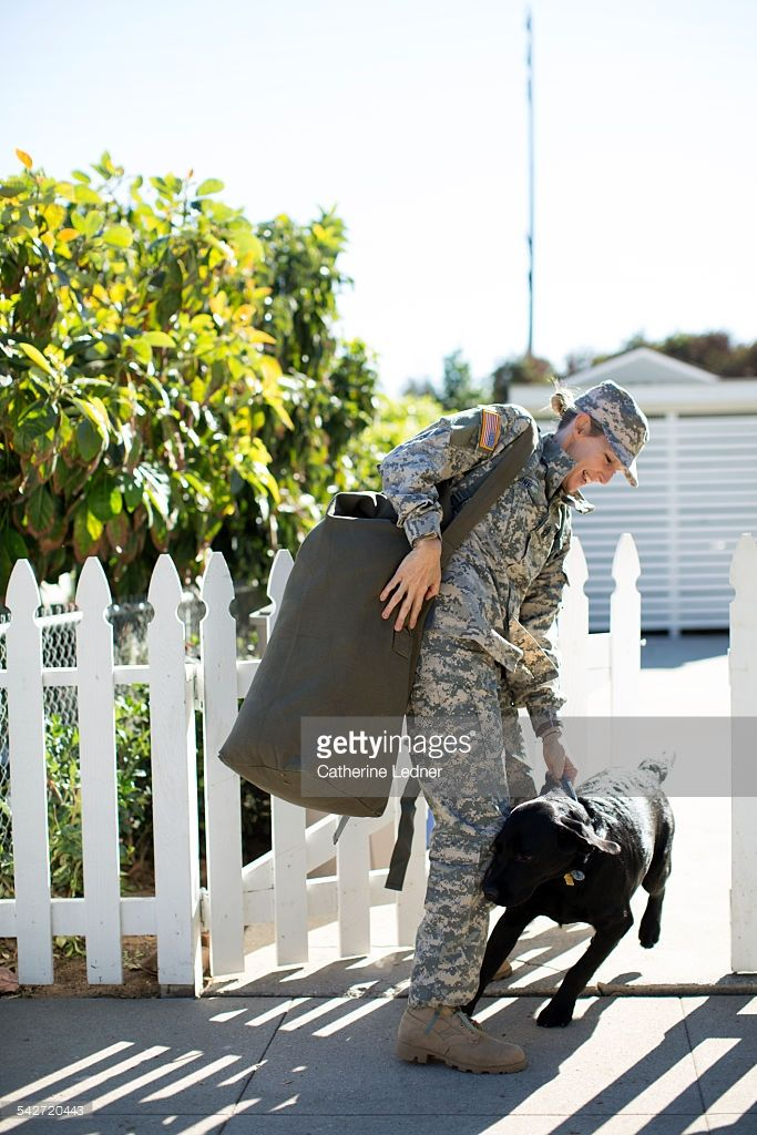Military Woman Carrying her Duffel Bag greeting her Labrador at Picket Fence