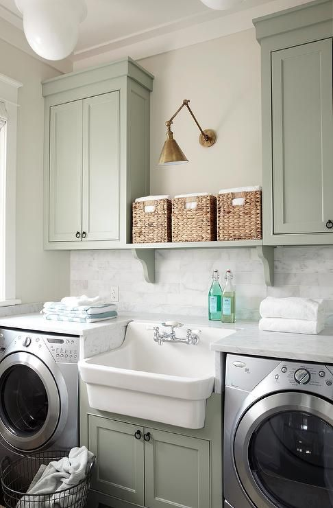 Cottage laundry room features green cabinets painted Sherwin Williams Oyster Bay paired with white marble countertops and a white marble subway tiled backsplash.