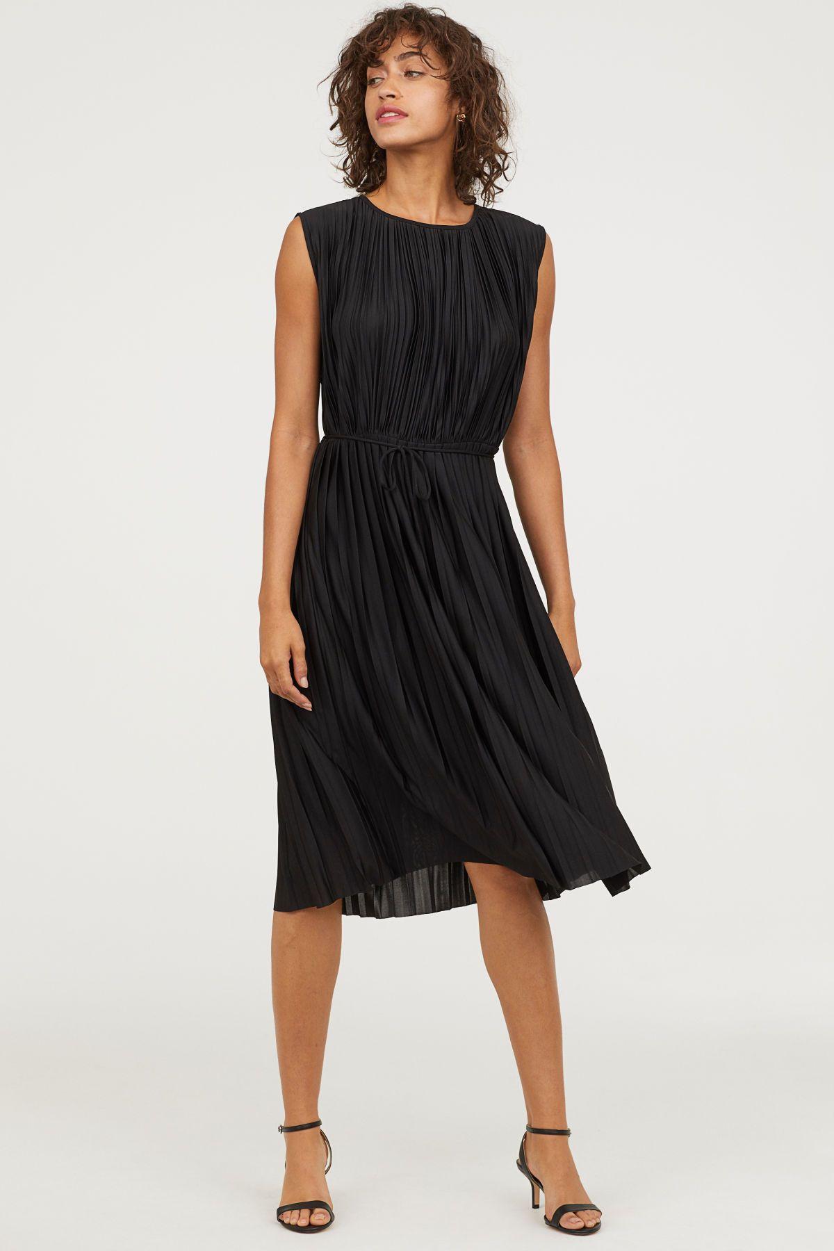 a7c0b4515703 Schwarz. Ärmelloses, knielanges Kleid aus plissiertem, glänzendem Jersey.  Das Kleid hat vorn einen Rundausschnitt und hinten einen V-Ausschnitt mit  Schmucke