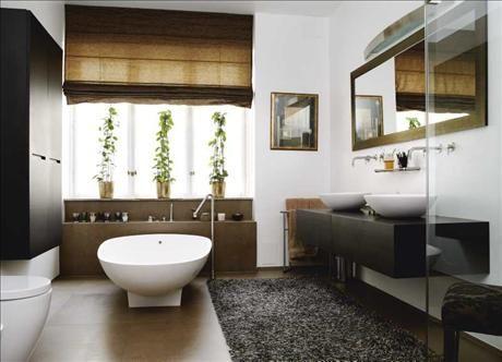 Badrummet har genomgående italiensk design, men med asieninspirerade detaljer som de skålformade handfaten och badkaret från Agape. Väggskåpet liksom bänken för handfaten kommer från Boffi. Spegeln är specialbeställd från Italien. Matta Kasthall, och gardin från Interiör.