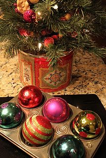Kitchen Decor: A used cookie tin and old muffin tin to display colorful Christmas tree and ornaments.