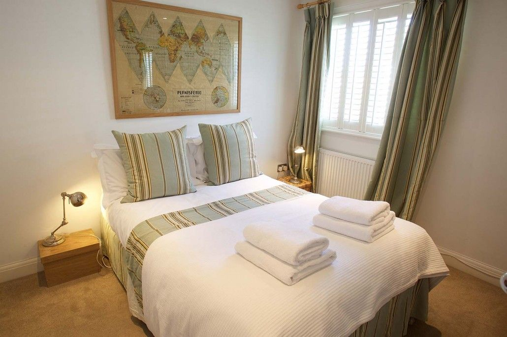 Mint and cream bedroom with world map poster. Angmering-on-Sea, West Sussex UK