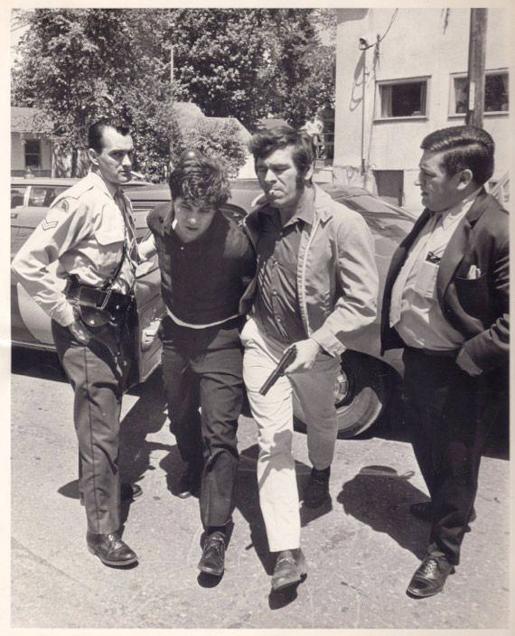 Undercover cop escorts a robbery suspect into the police station in the early 1970s